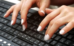 two hands typing at keyboard